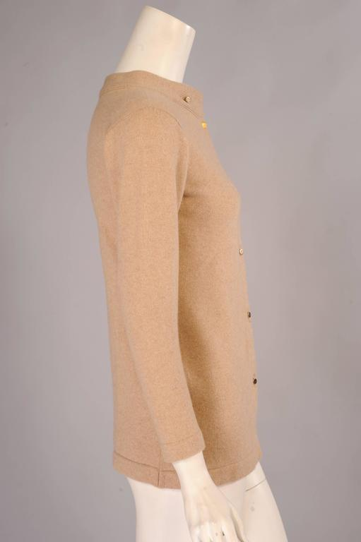 Natural Scottish Cashmere in at least a 4 ply thickness is used for this cardigan sweater from Bonnie Cashin. The long straight shape has a distinctive treatment at the neckline. The sweater has a stand up collar and two small gold toned buttons