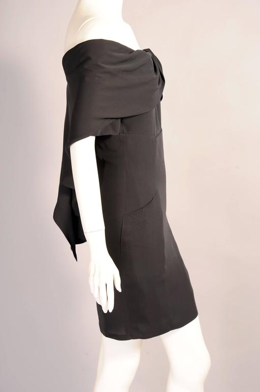 This sexy black silk cocktail dress from Chanel has an interesting draped off the shoulder neckline which cascades down the back of the dress. The dress has short sleeves, two pockets, a center back zipper and the drape closes with a hook and eye.