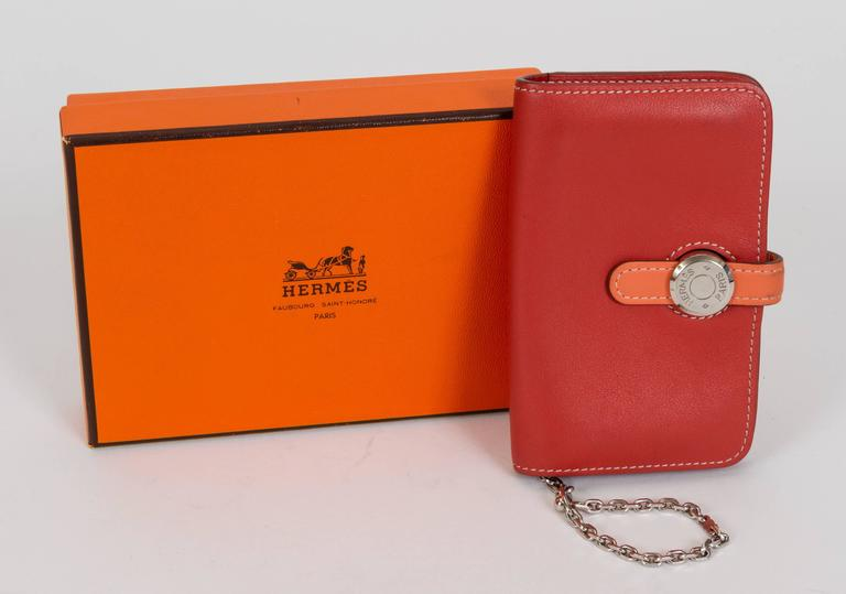 Hermès small dogon card wallet in bicolor swift leather and palladium hardware. Brick and coral combination. Date stamp Q for 2013. Comes with original box.