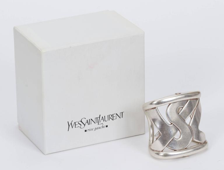 "YSL signature logo cuff bracelet with original box. Oversize heavy metal cuff with square fit around wrist. Great condition with minor wear. Opening is 1.25"" and inside diameter is 7"""