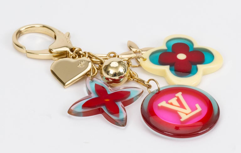 Louis Vuitton authentic bag charm /keychain with multicolor monogram symbols in lucite and gold tone metal. Comes with velvet pouch.