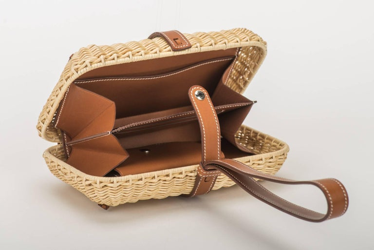 New in box natural woven wicker Hermès Picnic clutch with palladium hardware and barenia leather trim, single flat shoulder strap, tonal leather lining, dual interior compartments, dual slit pockets at interior walls, four card slots and snap