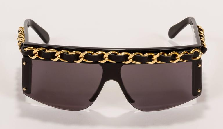 1980s Chanel black oversize celluloid sunglasses with gold-plated chain interlaced with black lambskin on top and sides. Comes with Chanel leather case and box. Minor scratches on frame and lenses.