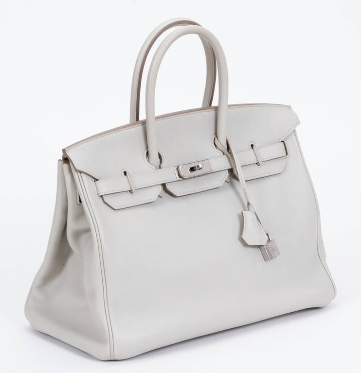 """Hermès Birkin 35cm in gris perle swift leather and palladium hardware. Date stamp """"O"""" for 2011. Minor scuffs on corners. Handle drop, 4.5""""L. Comes with clochette, tirette, lock, keys, and original dust cover."""