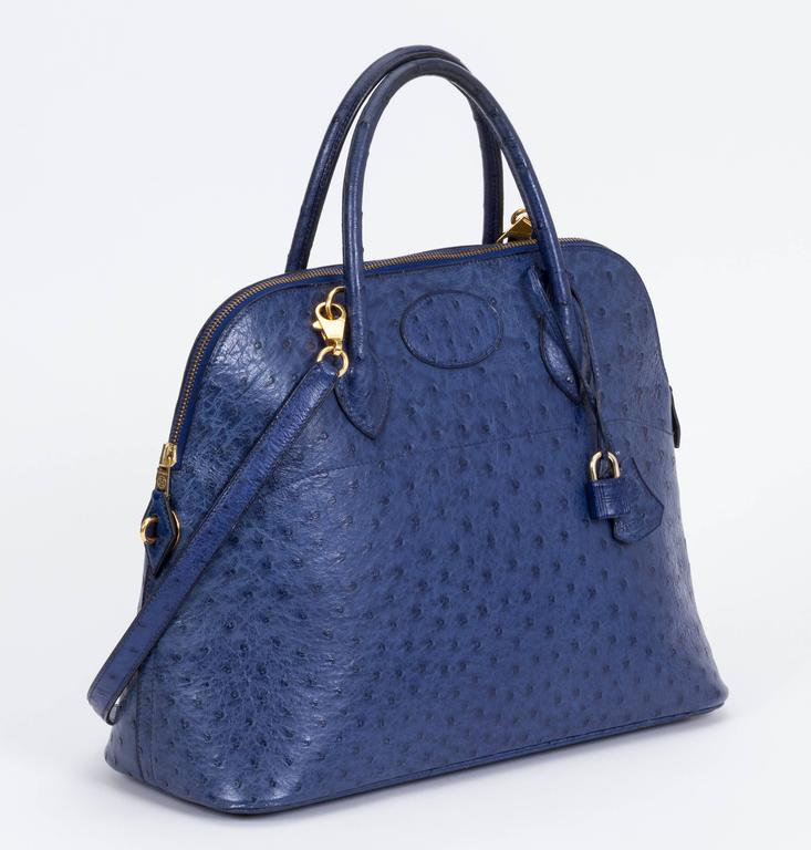"Hermès blue35cm ostrich Bolide bag. Gold hardware. Comes in duster, with lock, key and optional chain strap. Leather interior with pocket. Date stamped circled X for 1994. Handle drop, 4""L; strap, 35""L x .65""W."