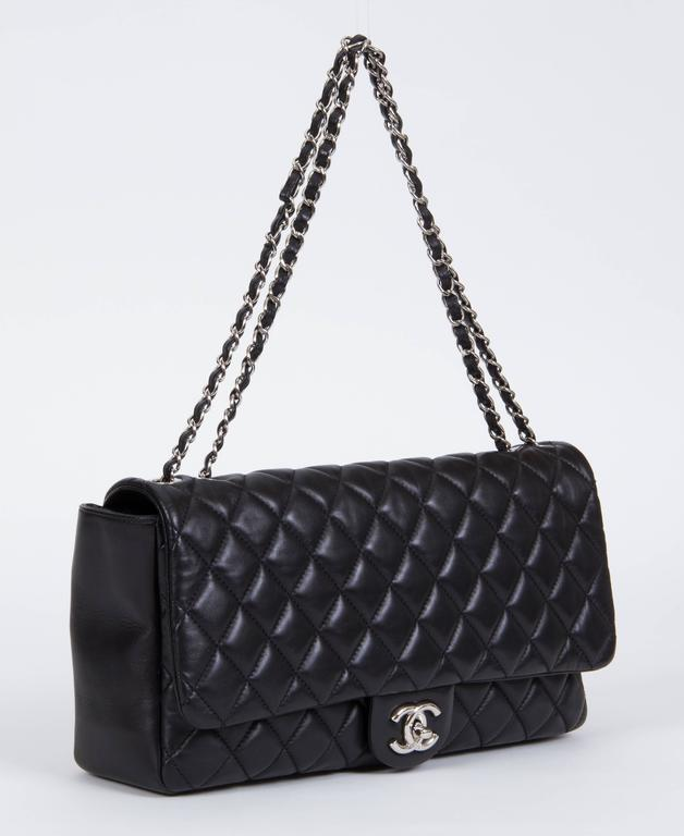 Chanel limited edition black lambskin quilted jumbo flap with silver tone hardware. Special edition with retractable rain jacket. Measurements: 13