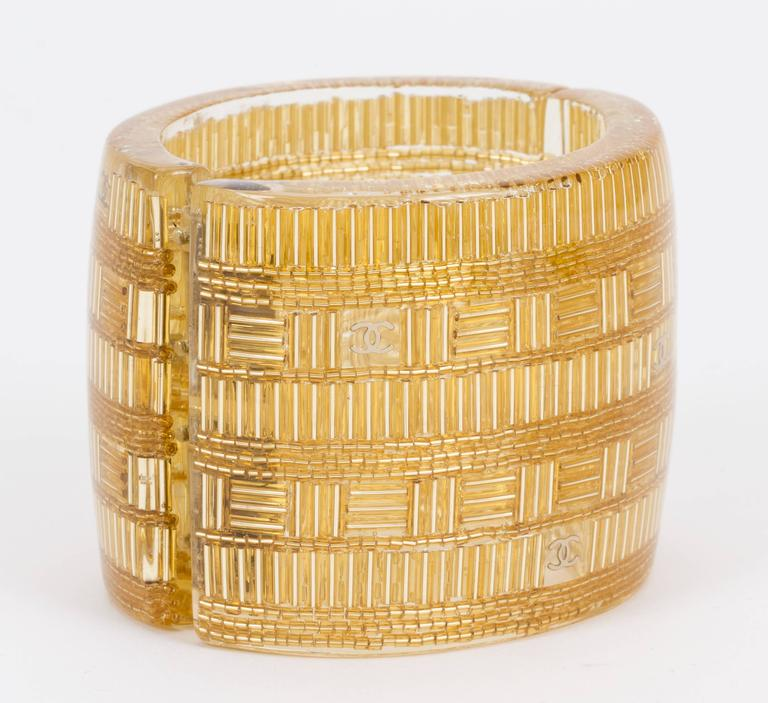 Chanel spring 2015 hinged lucite cuff bracelet. Gold and clear combination. Interior diameter 2 1/4
