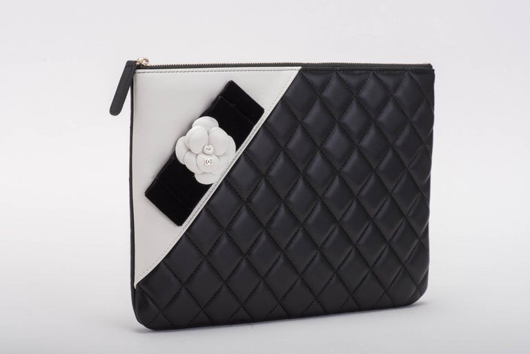 Chanel brand new in box timeless black and white quilted camellia clutch. Signature logo camellia with black velvet ribbon. Comes with hologram, ID card, booklet, box and ribbon.