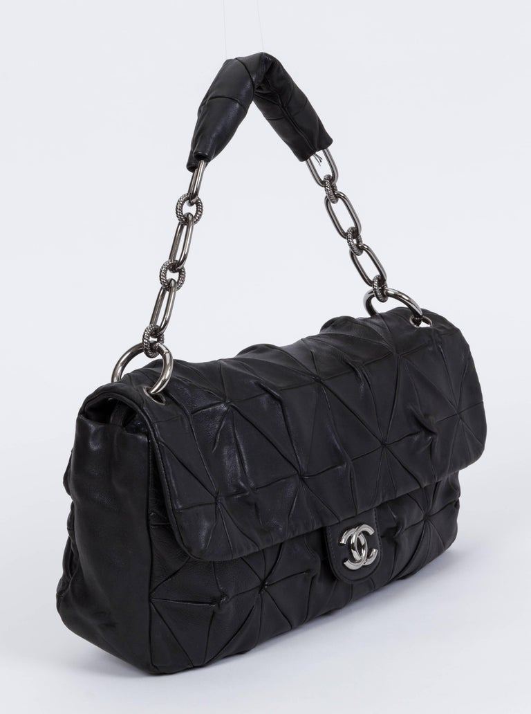 Chanel maxi single flap in black lambskin with silver tone hardware. Origami original quilting. Shoulder drop 8