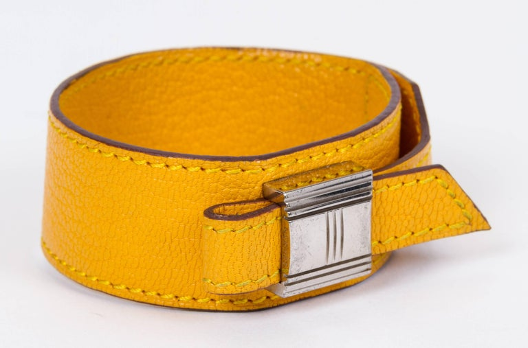 Vintage Hermès yellow leather bracelet palladium hardware slide. Fits any size. Gold hardware in excellent condition. Date stamp F for 2002. Comes with original box. Minor wear on the interior.