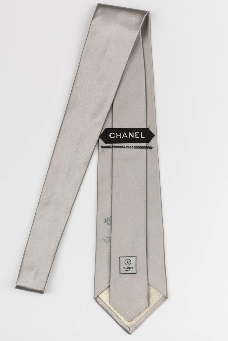 Chanel new in the original packaging and in excellent condition; Silver solid silk tie with oversize CC logo detail.