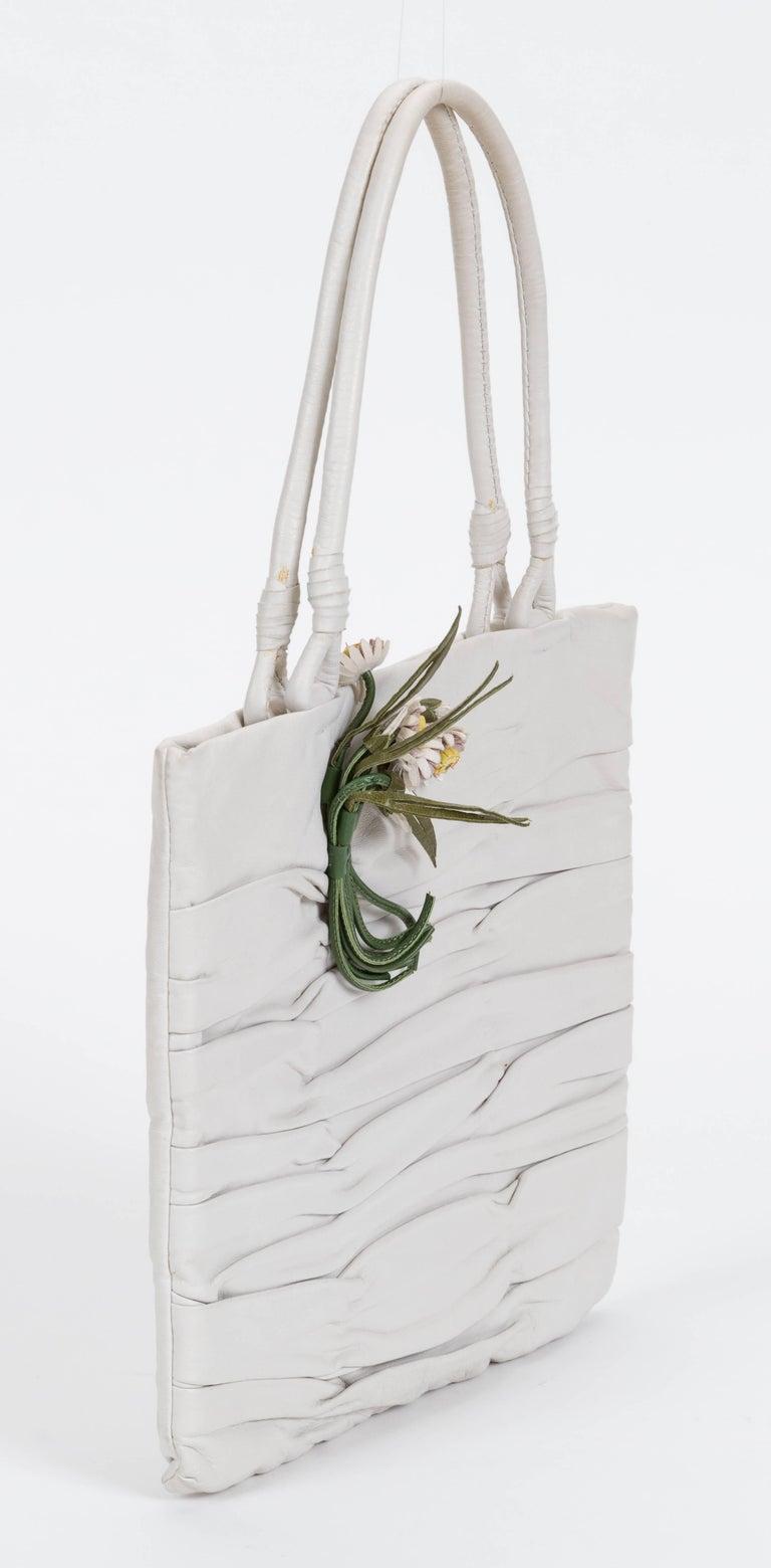Prada 90s vintage white lambskin handbag with flower detail. Green silk interior. One minor stain on back of the bag. Handle drop 5.5