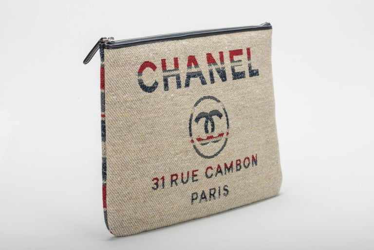New in Box Chanel large linen deauville clutch in beige, red and blue linen. Comes with hologram, id card, dust cover, box and ribbon.