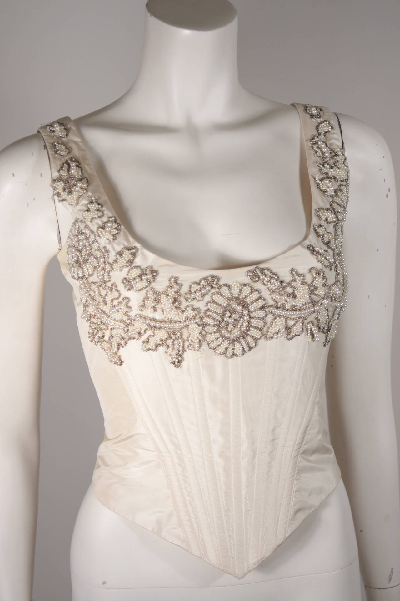 This Eavis & Brown London bustier is composed of a cream silk which is embellished with white and silver hued beading. Features a lace back. Made in London. 
