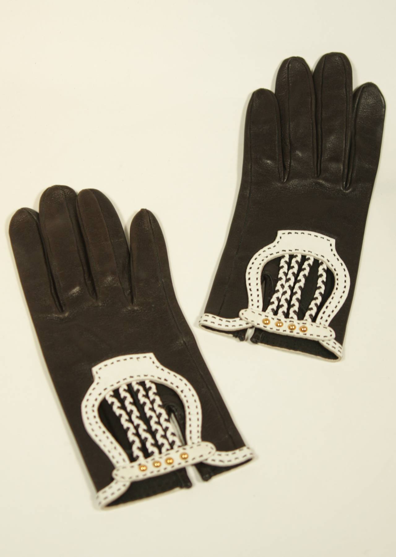 These Hermes gloves are composed of an exquisitely soft black leather with white accents and gold hardware. A beautiful design with braid detailing in excellent condition. Size 6.5