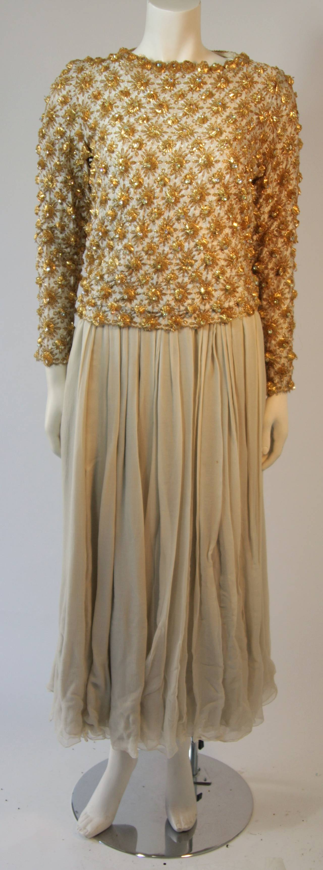 """This vintage gown features a gold embellished shell with a silk dress. There is a zipper closure. The dress is sold """"As Is"""".   Measures (Approximately) Shell Length: 19.75"""" Sleeve: 23.5"""" Shoulder to shoulder: 15 1/8"""" Bust: 36"""" Waist:"""