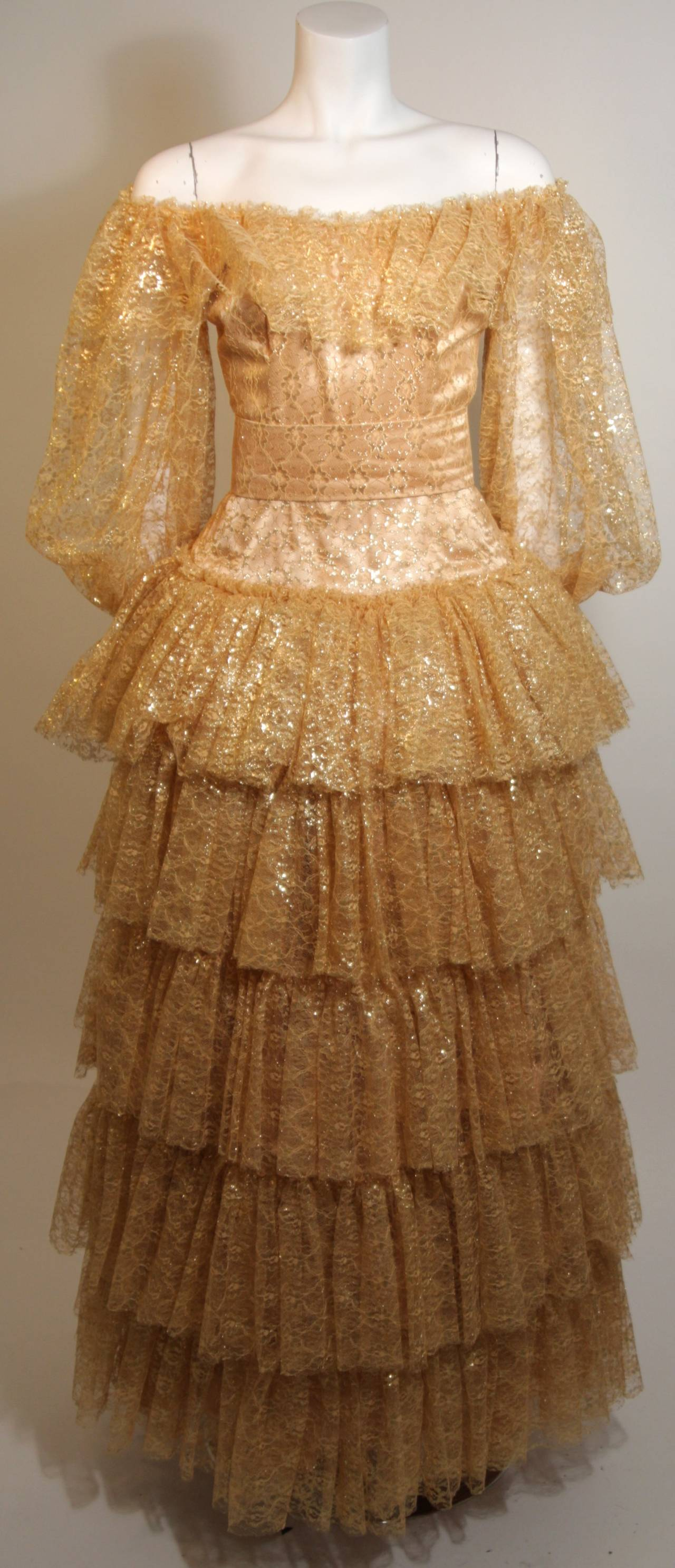 A dream of gold lace has a fully lined fitted bodice and sheer lace sleeve with elastic at the wrists. The tiered skirt was accented with a crinoline for the photographs and is sold separately.  The gown can be worn on or off-the-shoulders as there