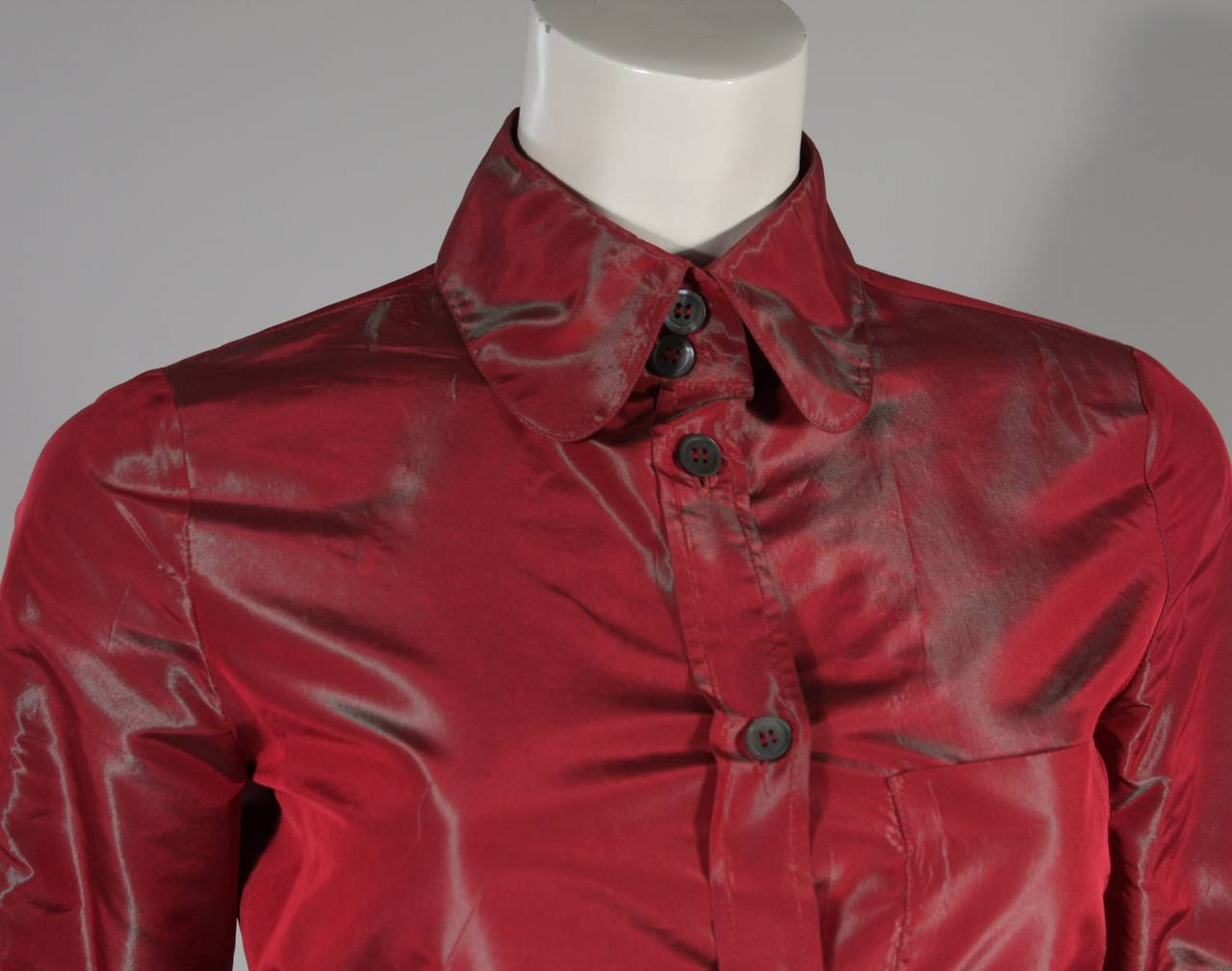 This Romeo Gigli blouse is composed of an red-iridescent fabric with center front button closures. Made in Italy. 