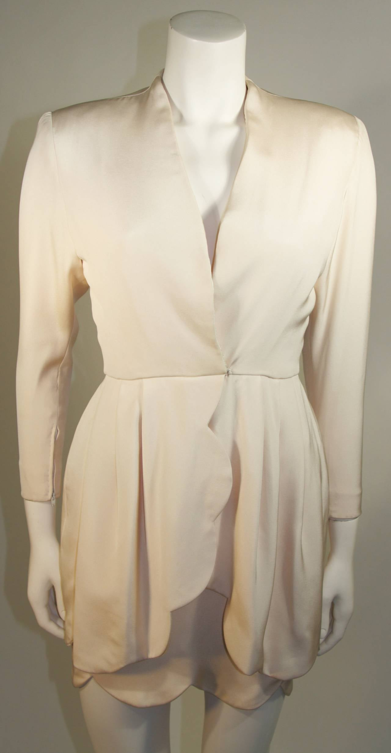 This gown is attributed to Valentino for Ira Berg dress is composed of a cream silk with a fabulous scalloped edge. The closure is at the center front which features a zipper and hook and eye closure. Made in France.   Measures