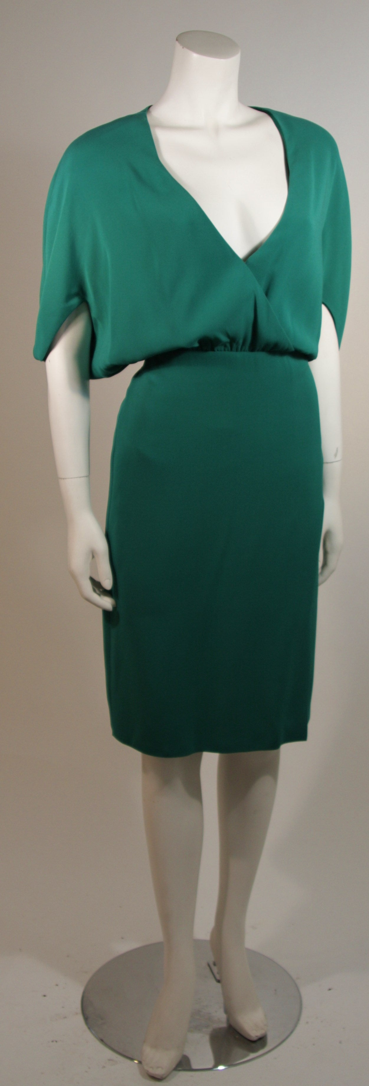 This Valentino dress is composed of a stunning green silk with a striking plunge neckline. There are batwing style sleeves, a hook and eye option at the bust, and a side zipper closure. Made in Italy.   Measures (Approximately) Length: 43