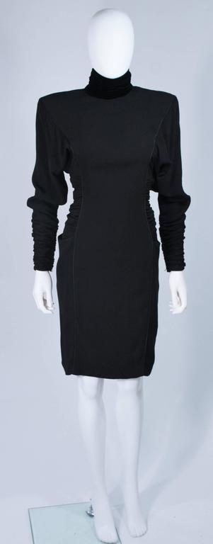 This Emanuel Ungaro dress is composed of a black silk with princess piping details and features a velvet mock collar. There is rouching and gathering at the sides and sleeves. Side pockets and a center back closure with faceted black buttons. In