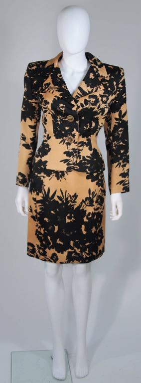 This Givenchy Couture skirt suit is composed of a apricot brown and black floral print fabric. with silk lining. The jacket has large rhinestone button closures. The pencil style skirt has a zipper closure. In excellent vintage condition.