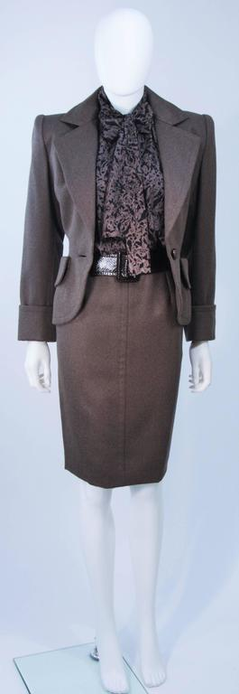 This Givenchy Couture skirt suit is composed of brown wool, a printed silk blouse, and a snakeskin belt. The jacket has center front button closures, structured shoulders, and front pockets. The printed silk blouse features center front button
