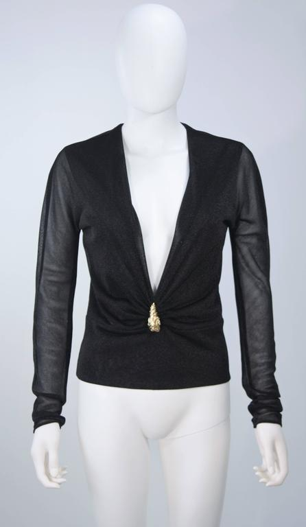 This Gucci blouse is composed of a stretch Lurex in black. Features a plunging neckline with gold lion head hardware. In excellent vintage condition. 
