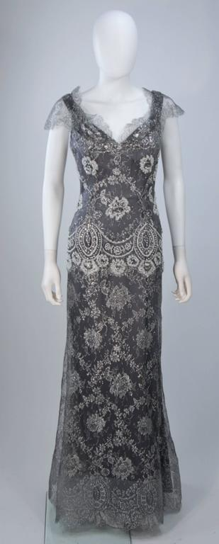 This Fe Zandi  gown is composed of a silver lame lace with scalloped edges. Features a draped neckline with sheer sleeve. There is a center back zipper closure, horse hair hem, and silk lining. In excellent vintage condition.   **Please