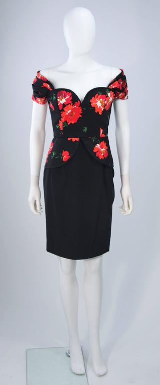 This Andrea Odicini  cocktail dress is composed of a black floral print silk with a bias cut edge (piping). The off the shoulder style design is accented by a structured peplum detail at the waist. Feature a structured neckline with a side zipper