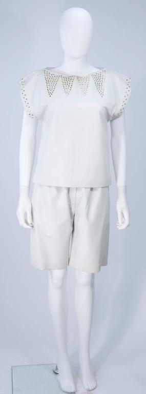 This Ted Lapidus short set is composed of an off white leather with gold studs. The blouse is a pull over style. The shorts feature a pleated front, side pockets, and zipper closure. In excellent vintage condition.