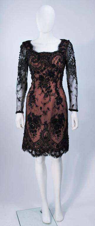 This Fe Zandi  cocktail dress is composed of black lace with a nude tone silk base. The lace features beaded applique with sequins and a scalloped edge. There are sheer sleeve, with a center back zipper closure. In excellent vintage condition.