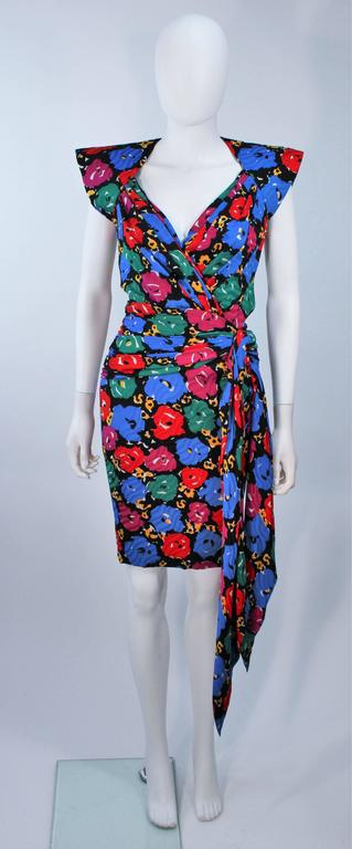 This Andrea Odicini cocktail dress is composed of a printed silk with floral print in a primary color story. Features structured shoulder with a side drape design. There is a center back zipper closure. In excellent vintage condition.