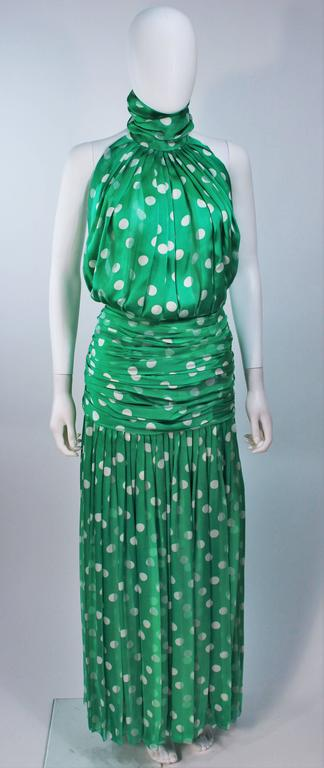 This Jiki  gown is composed of green and white polka dot silk. Features a halter mock neck with an open back, and a ruched waist to hip. There is a center back zipper. In excellent vintage condition.     **Please cross-reference measurements for