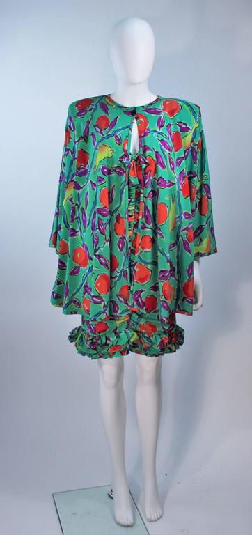 This Emanuel Ungaro set is composed of a printed teal silk with a floral and bird motif. The cocktail dress features a center front box and ruffled hem. The jacket has a hook and eye closure with a black faceted button closure. In excellent vintage