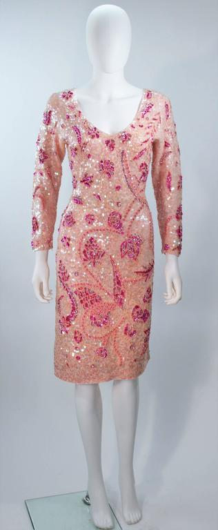 This Gene Shelly dress is composed of a pink stretch knit wool with pink and magenta sequin applique. There is a center back zipper closure. In excellent vintage condition. 