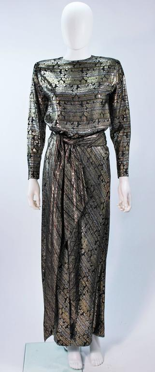 This Ron Leal  ensemble is composed of a metallic lame. The skirt portion of the dress features a bias cut. There is a  zipper closure and shoulder pads. In excellent vintage condition.     **Please cross-reference measurements for personal