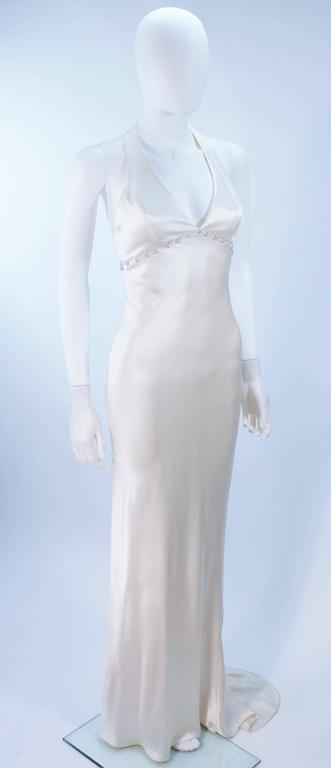 This Monique Lhuillier  gown is composed of a white bias cut silk and features a rhinestone applique at the empire waistline. There is a center back zipper closure, and train. In excellent vintage condition. 