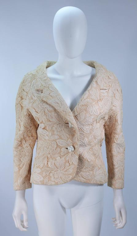 This Galanos jacket is composed of an off white cream hued floral lace. There are center front button closure with a wide neckline design. Silk lining. In excellent vintage condition. 