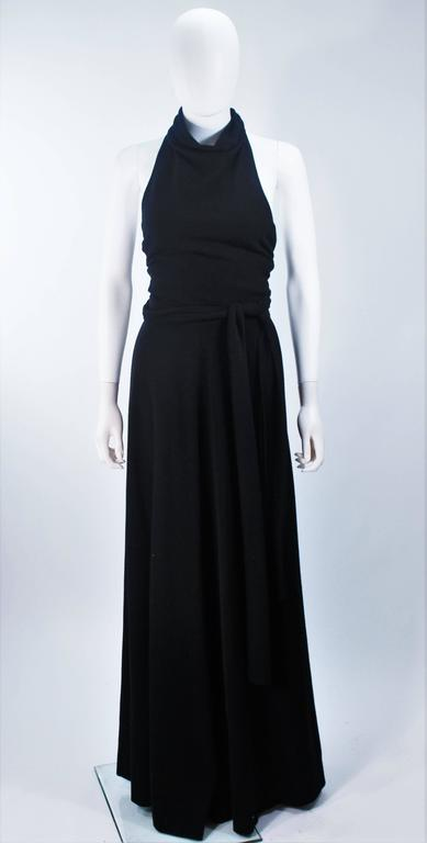 This Jean Patou  dress is composed of a light weight black wool. Features a draped halter style neck with open back, and waist tie. There is a zipper closure. In excellent vintage condition.    **Please cross-reference measurements for personal