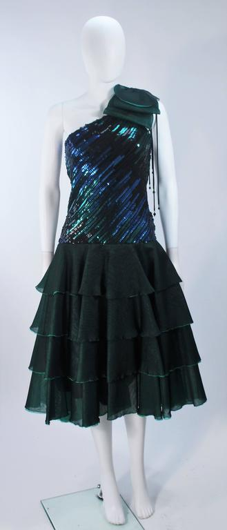 This dress is composed of a fine iridescent/multi-dimensional hue emerald green and teal silk with a sequin embellished bodice. Features an asymmetrical design with a side zipper. In excellent vintage condition. 