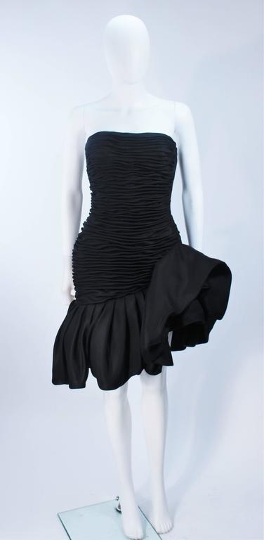 This Ungaro  dress is composed of a fine black silk with a gathered detail throughout the bodice and a dramatic ruffle detail. There is a center back zipper closure. In excellent vintage condition.     **Please cross-reference measurements for
