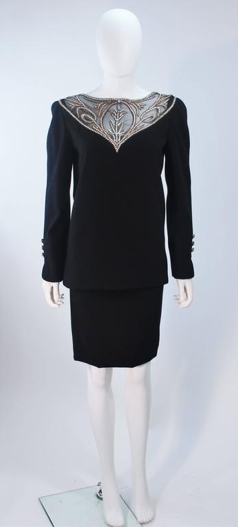 This Bob Mackie  ensemble is composed of a black wool with a sheer rhinestone accent at the upper neck and back. The blouse features a zipper closure. The classic pencil style skirt has a center back zipper closure. In excellent vintage condition.