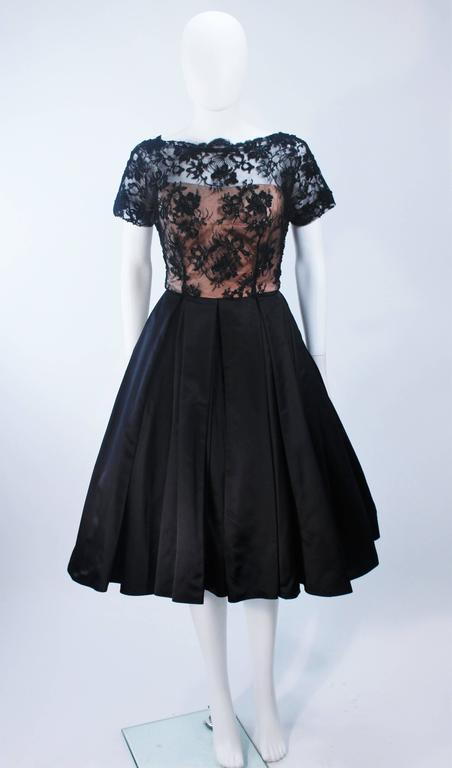 This cocktail dress is composed of black lace with silk. The bodice features scalloped edges with a nude underlay. The skirt is shot with crinoline (not included). There is a zipper closure with hook and eyes. In excellent vintage condition.