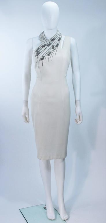 This vintage Sydney North cocktail dress is composed of a white crepe and features an asymmetrical halter design. There is a center back zipper closure. In excellent vintage condition.   **Please cross-reference measurements for personal