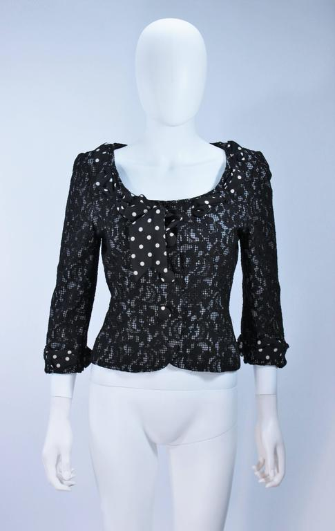 This Moschino  jacket is composed of a mixed combination of fabric patterns, there is a gingham base with a lace overlay and a silk polka dot scarf detail. There are center front closures. In great condition.   Measures (Approximately) Length: