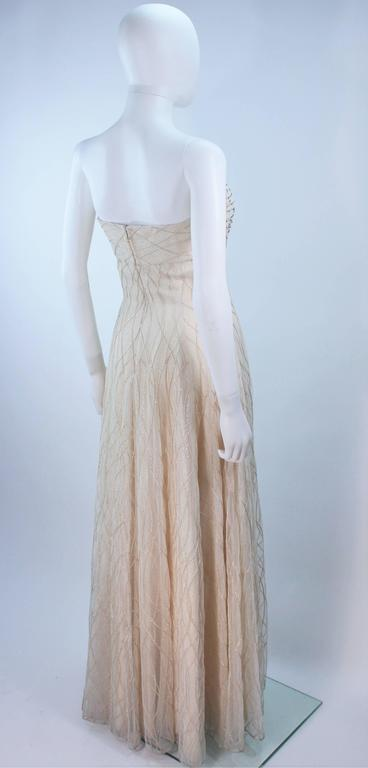 This Victor Costa  gown is composed of an off white layered mesh with iridescent cascading beaded applique. There is a center back zipper closure with interior boning and bra. In great vintage condition. 