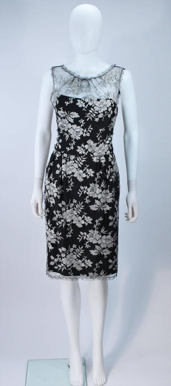 This Monique Lhuillier  cocktail dress is composed of a black and silver lace, with silk lining. Features scalloped edges with a center back zipper closure and key hole opening. There is interior boning and side pockets. In great condition.