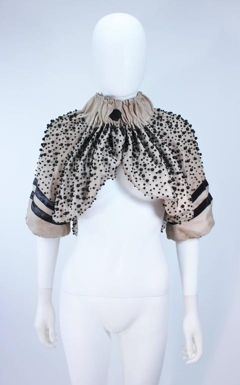 This Moncler  jacket is composed of a brown-nude mesh in a gathered fabrication with sequin and beaded applique. There is a center front snap closure. In great like new condition.     **Please cross-reference measurements for personal accuracy.