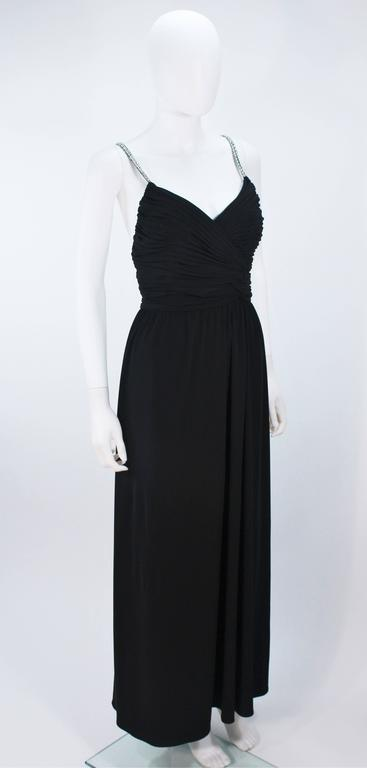 This Victoria Royal gown is composed of a black draped jersey with rhinestone straps. Features a draped design with center back zipper and criss-cross straps. Lined. In great vintage condition.    **Please cross-reference measurements for